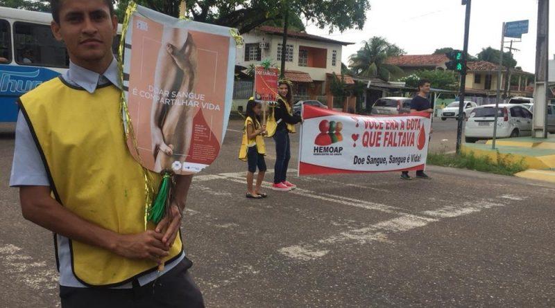 Voluntários com faixas em esquina para convocar pessoas para a doação — Foto: Ugor Feio/G1