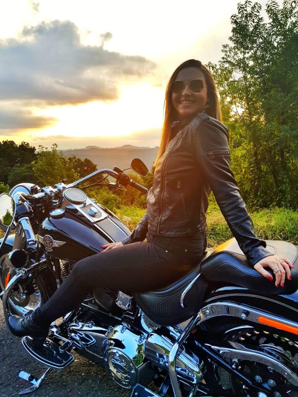 Cristalina sentada sobre uma moto.